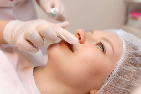 The cosmetologist prepares the client's lips for the augmentation procedure