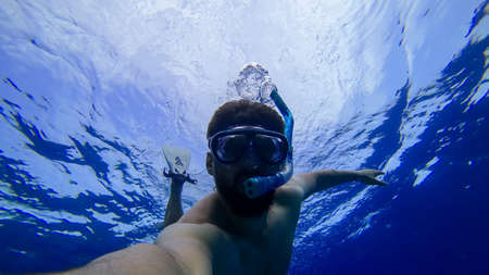 a man is engaged in snorkeling diving into the depths of the red sea in a mask and a breathing tube Zdjęcie Seryjne