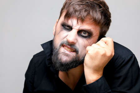Portrait of a man with a beard and a menacing look with undead-style makeup on All Saints' Day on October 31