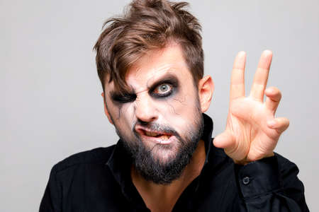 a man with undead makeup for Halloween holds his hands in front of him and looks at the camera from under his forehead Standard-Bild