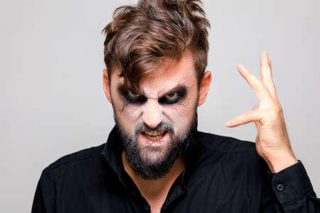 a man with a beard and makeup for Halloween grimaced Standard-Bild
