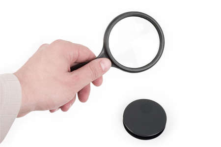 Black magnifying glass isolated against white background and male hand holding it