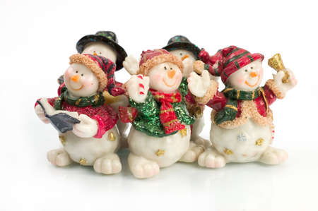 miniature Snowman statues in different poses against white background with clipping paths