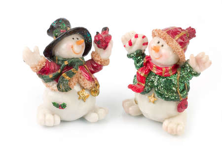 miniature Snowman statues in different poses against white background