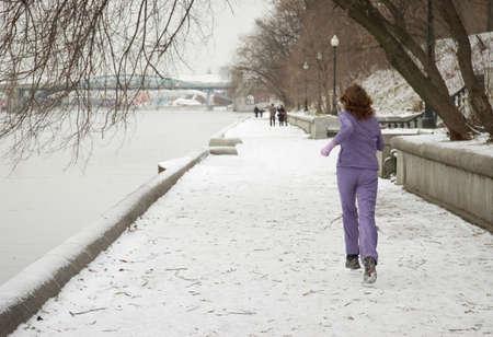 Woman jogging at river embankment. Winter