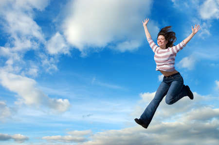 Beautiful woman jumping against blue sky Stock Photo