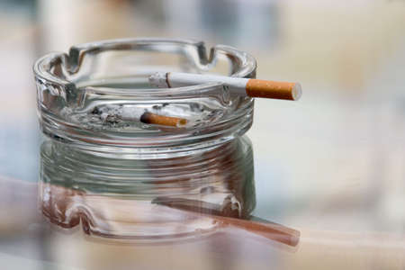ashtray: Ashtray with cigarette on a reflecting surface of a glass table in a cafe