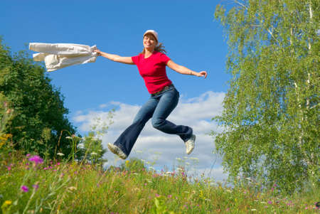 Beautiful lady jumping in summer landscape