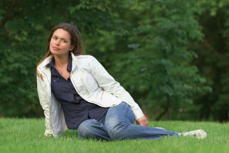 Pretty brunette relaxing on a fresh grass in a park Stock Photo