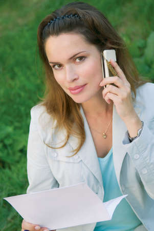 Beautiful woman talking by the mobile phone outdoors Stock Photo