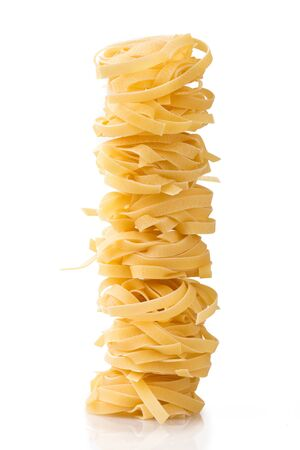 Column of raw tagliatelle on white background photo
