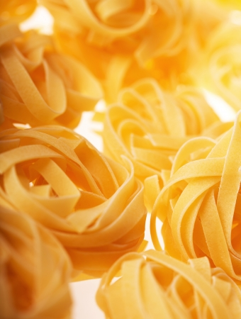 Raw tagliatelle on white background photo