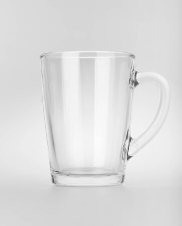 Empty clear glass mug with reflections on background photo
