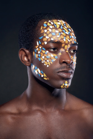 bronzed: Beauty portrait of handsome ethnic african male with creative make-up