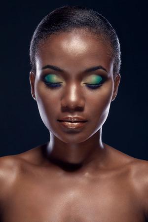 ojos negros: Retrato de la belleza de la hermosa ni�a africana �tnica con los ojos cerrados, sobre fondo oscuro