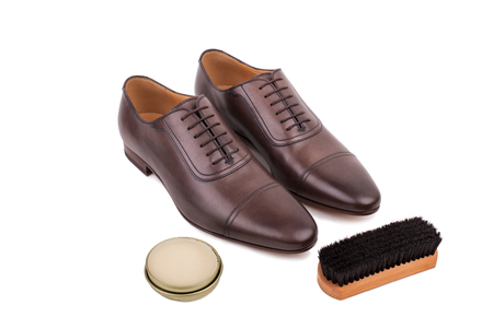 brogues: Pair of new brown leather male shoes with shoe care kit, brush and shoe wax Stock Photo