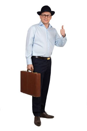 Full length portrait of Young businessman with hat and glasses wearing blue shirt and trousers. Holding brown leather suitcase and gesture of thumb up. Studio shot on white background.