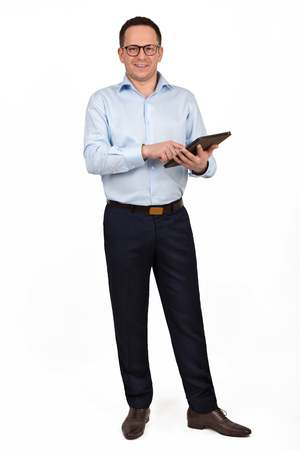 Young prosperous business man dressed in shirt and trousers work on digital tablet, skilled male entrepreneur dressed in corporate clothes using touch pad while standing in white background
