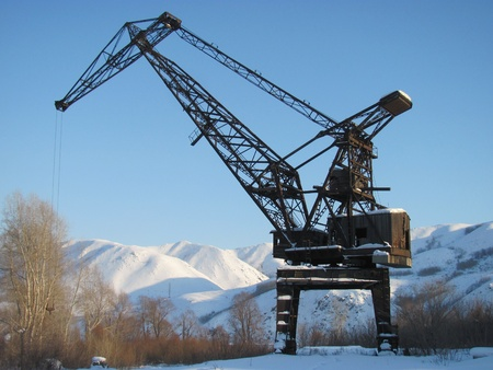The elevating crane big high and old, with a wooden cabin and an engine room, against the blue sky and mountains covered with snow. Stock Photo