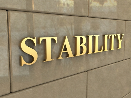 The word Stability is chiseled by gold letters on a stone wall. Stock Photo