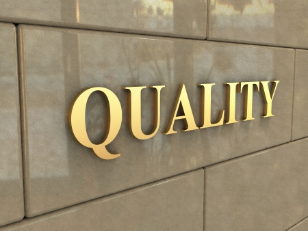 The word Quality is chiseled by gold letters on a stone wall. Stock Photo