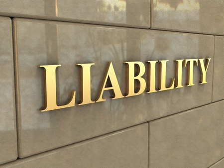 Word Liability. The word Liability is chiseled by gold letters on a stone wall. Stock Photo