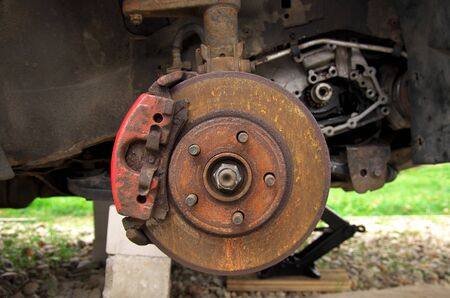 rusty brake disc on a broken car in the yard. broken car on the Jack and on the bricks