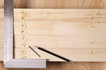 draw a layout of the wood. pencil and set square for accurate marking of the holes. Stockfoto