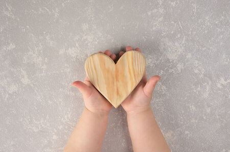 children's hands holding natural wooden heart. a gift on Valentine's day. abstract silver background.