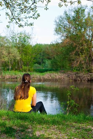 river bank: girl sitting on the bank of the river