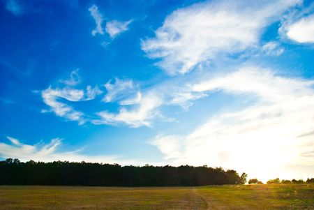 beautifull landscape with sun, sky, clouds and meadow photo