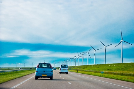 cars on a highway with wind turbines Stock Photo