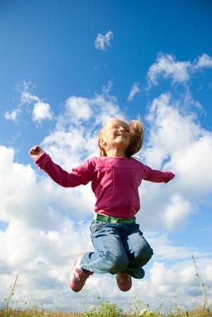 meisje springen in de wei Stockfoto