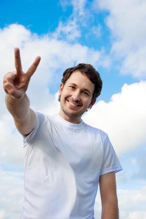 男の勝利記号に対して青い空を身振りで示す