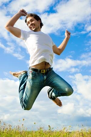saltando: hombre que salta en un prado Foto de archivo