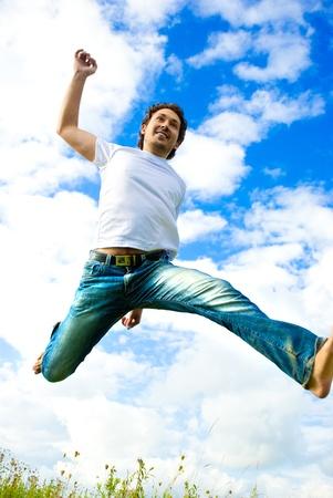 hombres corriendo: hombre que salta en un prado Foto de archivo