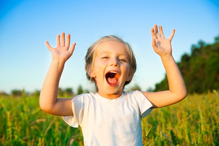 mouth  open: little girl screaming in a meadow with hands up Stock Photo