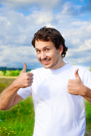 man showing two thumbs up on a meadow photo