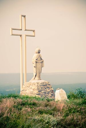 mother mary statue and cross outdoors photo