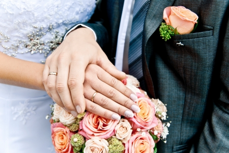 hands of bride and groom over wedding bouquet photo