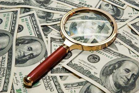 ドルの背景に置かれた虫眼鏡