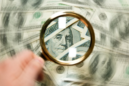magnifying glass with background of dollars photo