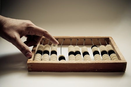 old abacus with human hand photo