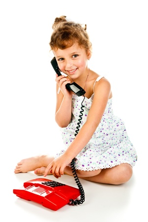 little girl sitting: little girl with telephone isolated on a white background Stock Photo