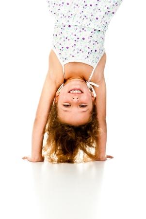 little girl upside down on a white background Standard-Bild