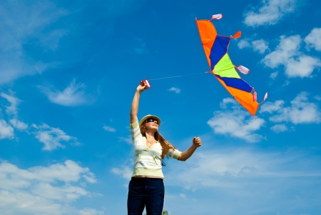 woman with kite against the blue sky Stock Photo