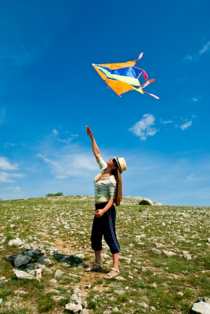 woman with kite against the blue sky photo