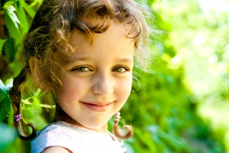 smiling little girl with green leaves outdoors photo