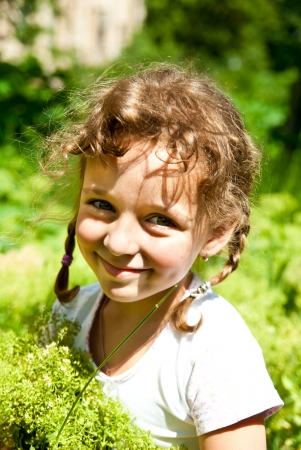smiling little girl with green grass outdoors photo