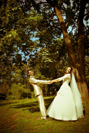 bride and groom standing in the park photo